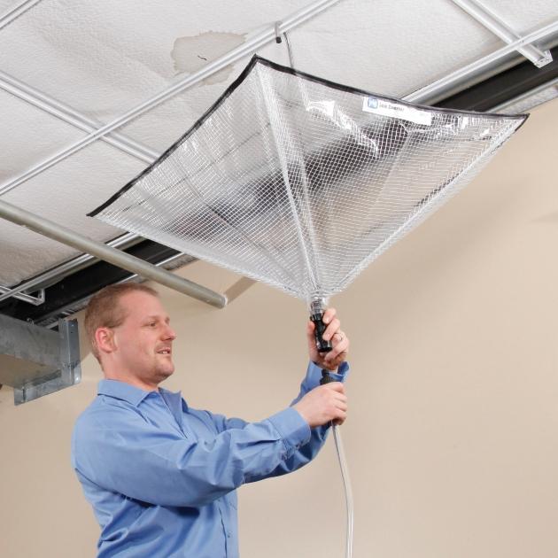 man hanging leak diverter tarp from ceiling