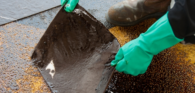 Person holding used oil absorbent mat during spill cleanup